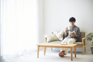 ソファとテーブルが置かれた部屋でくつろぐ男性の写真素材 [FYI04606436]