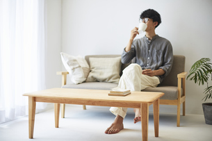 ソファとテーブルが置かれた部屋でくつろぐ男性の写真素材 [FYI04606437]