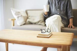 ソファとテーブルが置かれた部屋でくつろぐ男性の手元の写真素材 [FYI04606439]