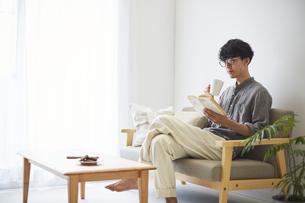 ソファとテーブルが置かれた部屋で本を読む男性の写真素材 [FYI04606441]