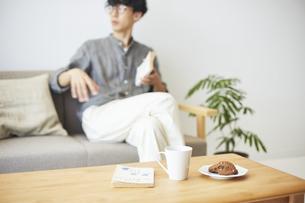 ソファとテーブルが置かれた部屋でくつろぐ男性の写真素材 [FYI04606442]