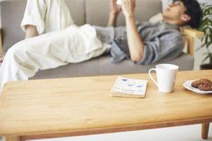 ソファとテーブルが置かれた部屋で本を読む男性の写真素材 [FYI04606443]
