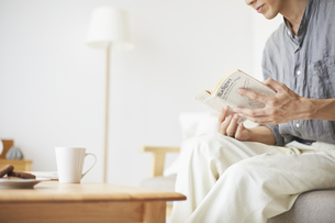 本を読む男性の手元の写真素材 [FYI04606446]
