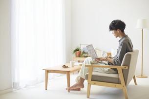 ソファとテーブルが置かれた部屋でパソコンを操作する男性の写真素材 [FYI04606449]
