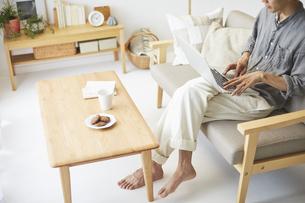 ソファとテーブルが置かれた部屋でパソコンを操作する男性の写真素材 [FYI04606450]