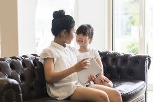 タブレットで遊ぶ姉妹の写真素材 [FYI04606588]