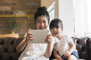 タブレットで遊ぶ姉妹の写真素材 [FYI04606589]