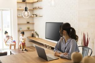 在宅勤務する母とリビングで遊ぶ子供たちの写真素材 [FYI04606611]