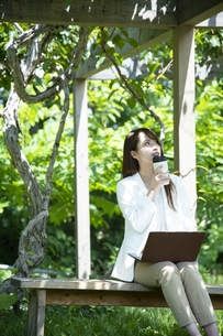 パーゴラの下で仕事をする若い女性の写真素材 [FYI04606613]