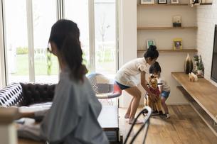 リビングで遊ぶ子供たちと見守る母の写真素材 [FYI04606627]