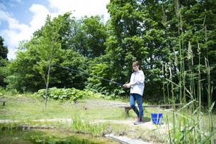 釣りを楽しむ若い女性の写真素材 [FYI04606667]