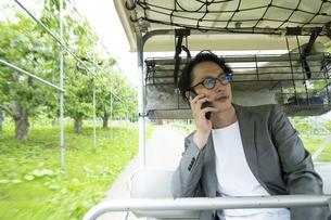 ゴルフカートに乗って仕事をするミドルの男性の写真素材 [FYI04606685]