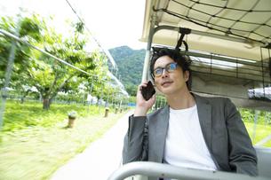 ゴルフカートに乗って仕事をするミドルの男性の写真素材 [FYI04606686]