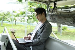 ゴルフカートに乗って仕事をするミドルの男性の写真素材 [FYI04606687]