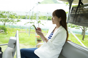 ゴルフカートに乗って仕事をする若い女性の写真素材 [FYI04606688]