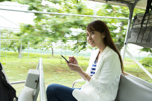 ゴルフカートに乗って仕事をする若い女性の写真素材 [FYI04606689]