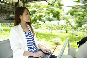 ゴルフカートに乗って仕事をする若い女性の写真素材 [FYI04606690]