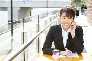 カフェで電話をしているスーツ姿の女性の写真素材 [FYI04606845]