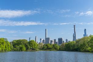 セントラルパーク生い茂る新緑に囲まれたザ レイクの後ろに見えるミッドタウンマンハッタンの摩天楼の写真素材 [FYI04606926]