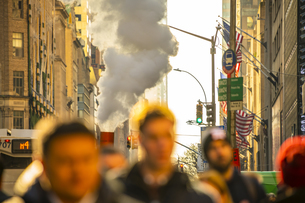 クリスマスホリデーシーズンのミッドタウン五番街高層ビル群の間を漂う蒸気と人々の写真素材 [FYI04606968]