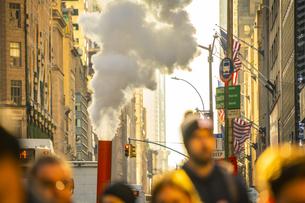 クリスマスホリデーシーズンのミッドタウン五番街高層ビル群の間を漂う蒸気と人々の写真素材 [FYI04606971]
