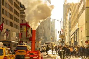 クリスマスホリデーシーズンのミッドタウン五番街高層ビル群の間を漂う蒸気と人々の写真素材 [FYI04606976]