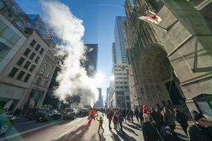 クリスマスホリデーシーズンのミッドタウン五番街高層ビル群の間を漂う蒸気。冬の太陽に照らされ漂う蒸気の中を交通と人々が行き交いますの写真素材 [FYI04607012]