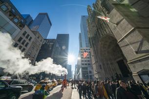 クリスマスホリデーシーズンのミッドタウン五番街高層ビル群の間を漂う蒸気。冬の太陽に照らされ漂う蒸気の中を交通と人々が行き交いますの写真素材 [FYI04607019]