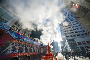 クリスマスホリデーシーズンのミッドタウン五番街高層ビル群の間を漂う蒸気。冬の太陽に照らされ漂う蒸気の中を交通と人々が行き交いますの写真素材 [FYI04607024]