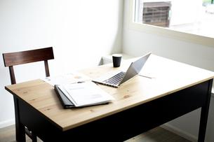 デスクの上のノートパソコンと書類とコーヒーの写真素材 [FYI04607059]