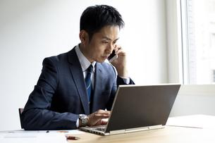 ノートパソコンを見ながらスマートフォンで話すビジネスマンの写真素材 [FYI04607060]