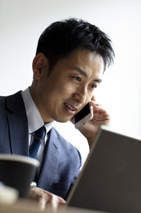 ノートパソコンを見ながらスマートフォンで話すビジネスマンの写真素材 [FYI04607063]