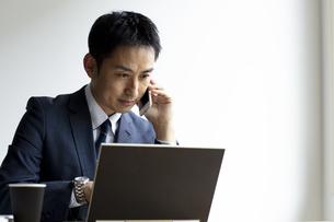 ノートパソコンを見ながらスマートフォンで話すビジネスマンの写真素材 [FYI04607064]