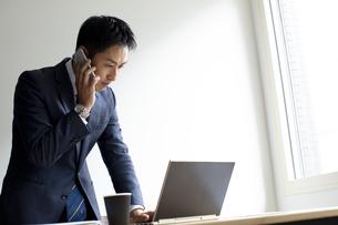 ノートパソコンを見ながらスマートフォンで話すビジネスマンの写真素材 [FYI04607065]