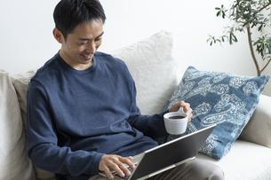 コーヒーカップを持ってノートパソコンを操作する日本人男性の写真素材 [FYI04607073]