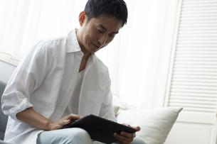 タブレットPCを見る日本人男性の写真素材 [FYI04607102]
