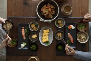 食卓の上の和食と食事をする夫婦の手の写真素材 [FYI04607144]