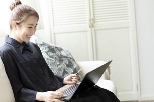 ノートパソコンでオンラインショッピングをする日本人女性の写真素材 [FYI04607166]
