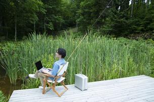池のほとりで仕事をするミドルの男性の写真素材 [FYI04607167]