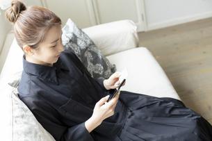スマートフォンでオンラインショッピングをする日本人女性の写真素材 [FYI04607168]