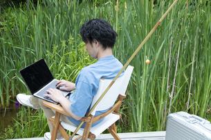 池のほとりで仕事をするミドルの男性の写真素材 [FYI04607172]