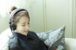ヘッドホンをつけてタブレットPCを見る日本人女性の写真素材 [FYI04607183]