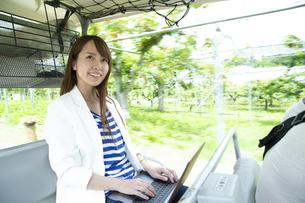 ゴルフカートに乗って仕事をする若い女性の写真素材 [FYI04607237]