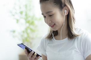 スマートフォンで音楽を聴く日本人女性の写真素材 [FYI04607252]