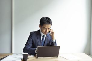 ノートパソコンを見ながらスマートフォンで話すビジネスマンの写真素材 [FYI04607256]