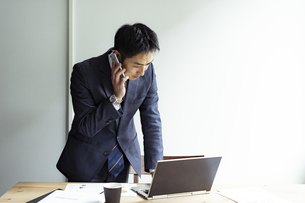 ノートパソコンを見ながらスマートフォンで話すビジネスマンの写真素材 [FYI04607260]