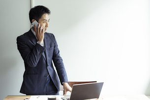 スマートフォンで話すビジネスマンの写真素材 [FYI04607261]