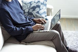 ソファーに座りノートパソコンを操作する男性の写真素材 [FYI04607271]