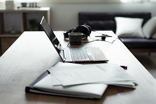 テーブルの上のノートパソコンと書類とインカムの写真素材 [FYI04607289]