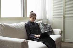 ソファーに座りノートパソコンを見る日本人女性の写真素材 [FYI04607329]
